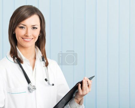 Smiling female doctor with clipboard at office
