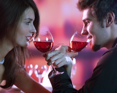 Photo for Young happy amorous couple with glasses of redwine on romantic date at restaurant - Royalty Free Image