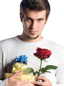 Young man with gifts and rose