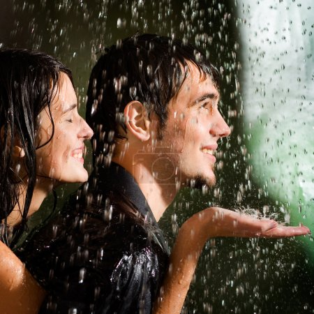 Young happy couple under a rain