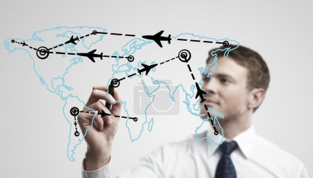 Photo for Young business man drawing an airplane routes on world map. Man drawing world map with aircraft flying on a glass window. - Royalty Free Image