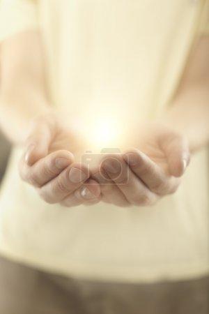 Photo pour Mâle mains tenue des rayons de l'éclatante lumière. énergie magique dans les mains. flou artistique - image libre de droit