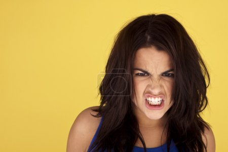 Head-shot of a young and angry woman on a yellow b...
