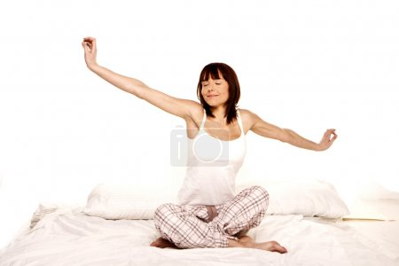 Photo for A young woman stretches as she wakes up from a good nights sleep. - Royalty Free Image