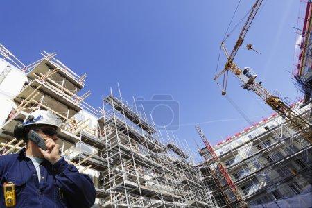 Photo pour Ingénieur de chantier avec construction d'échafaudages géants en arrière-plan, perspective large - image libre de droit