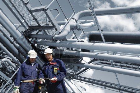 Photo pour Deux travailleurs du pétrole, ingénieurs, construction de grands pipelines en arrière-plan - image libre de droit