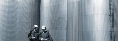 Photo pour Deux ingénieurs avec des réservoirs géants de pétrole et de carburant en arrière-plan, vue panoramique - image libre de droit