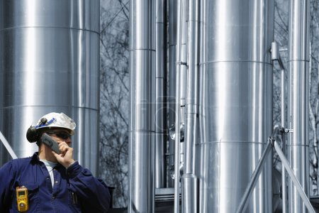 Photo pour Industrie pétrolière, gazière et des combustibles, personnel de raffinerie en arrière-plan, tubes à gaz et pipelines - image libre de droit