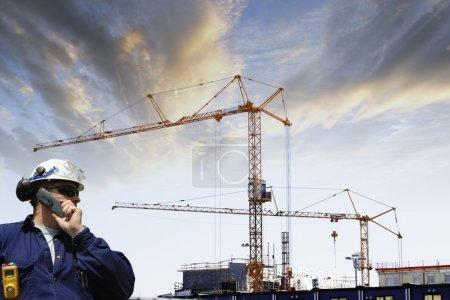 Photo pour Deux travailleurs du bâtiment avec une grue de construction géante en arrière-plan, paysage de chantier - image libre de droit