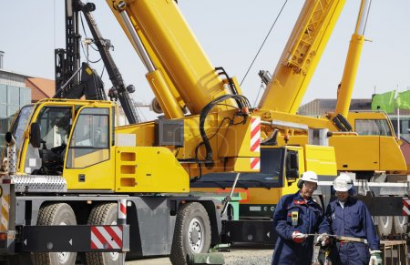 Photo pour Deux travailleurs de l'industrie avec deux grues mobiles géantes en arrière-plan - image libre de droit