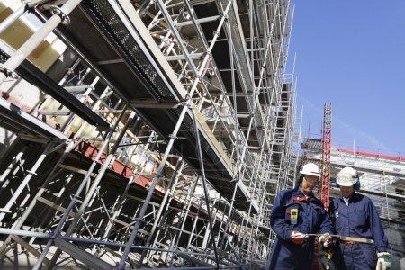 Photo pour Deux ouvriers marchant le long de grands échafaudages, concept industriel - image libre de droit