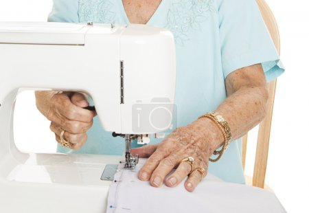 Photo for Senior woman's hands using her sewing machine. White Background. - Royalty Free Image