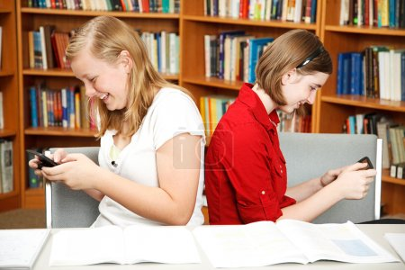 Photo for Teenage girls texting in the school library, instead of studying. - Royalty Free Image