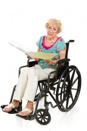 Photo pour Senior femme en fauteuil roulant, tenant une pile de factures. corps entier isolé sur blanc - image libre de droit