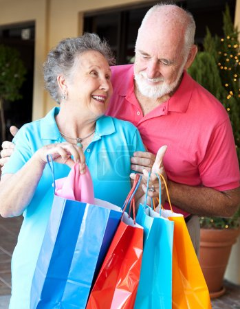 Photo for Senior man looks in the shopping bags to see what his wife has bought. - Royalty Free Image