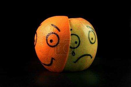 Photo for Sad apple with happy orange mask on black background - Royalty Free Image