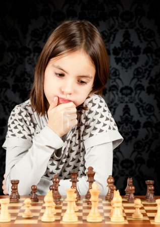 Photo pour Petite fille jouant aux échecs sur fond vintage - image libre de droit