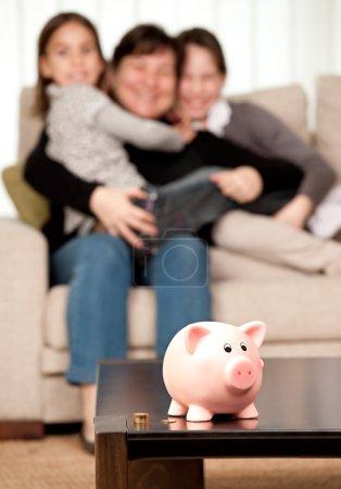Foto de Family saving money on a piggy bank - Imagen libre de derechos