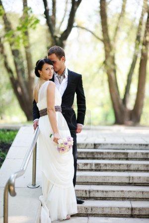 Photo pour Élégants mariés posant ensemble à l'extérieur le jour d'un mariage - image libre de droit