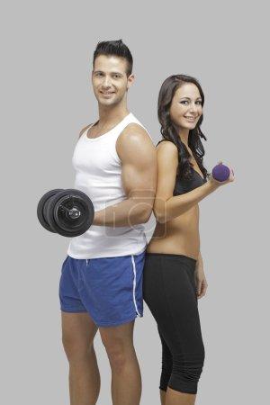 Foto de Entrenamiento de pareja feliz junto con pesas en sus manos - Imagen libre de derechos