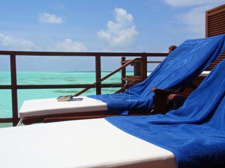 Photo pour Deux chaises longues sur une terrasse au maldives. - image libre de droit