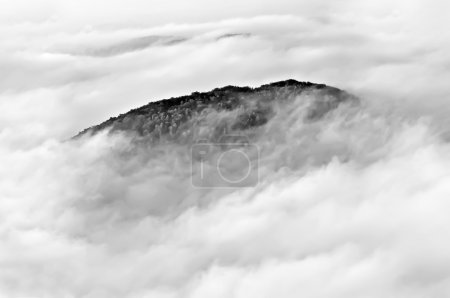 Photo pour Sommet de la montagne noyé dans les nuages, photo noir et blanc . - image libre de droit