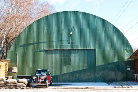 Old green aircraft hanger with classic car park in front