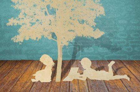 Photo pour Découpe de papier d'enfants lire un livre sous l'arbre - image libre de droit