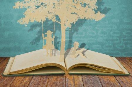 Photo pour Découpe de papier des enfants lire un livre et les enfants sur balançoire sous l'arbre - image libre de droit