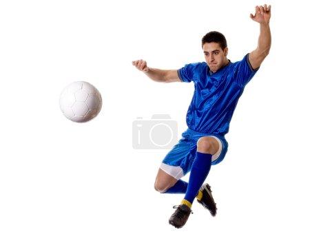 Soccer player kicking. Studio shot over white.