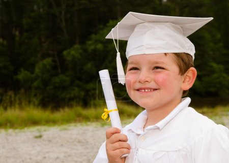 Young boy with cap and gown and certificate for preschool graduation