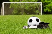 Kind-Sport-Konzept mit Fußball, Klampen, Schienbein Wachen auf Feld mit textfreiraum