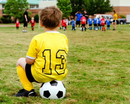 Photo for Young boy child in uniform watching organized youth soccer or football game from sidelines - Royalty Free Image