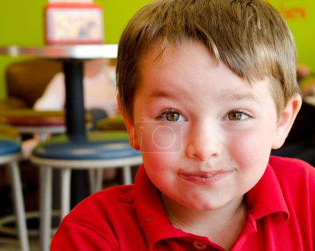 Young boy's face covered with chocolate after eating frozen yogurt at frozen yogurt or ice cream shop