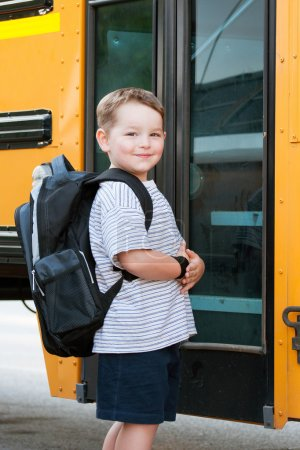 Happy young boy in front of school bus going back to school