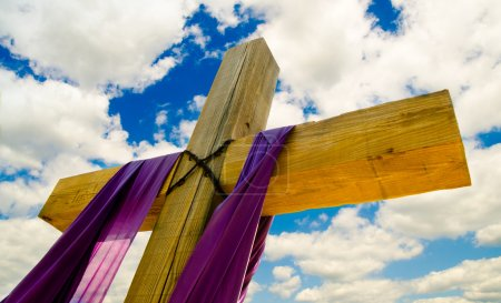 Cross with purple drape or sash for Easter with blue sky and clouds in background