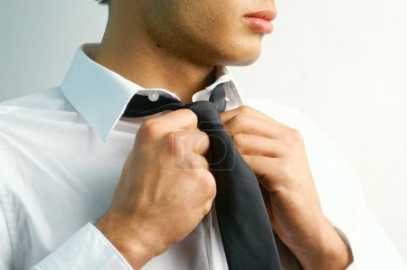 Portrait of a handsome stylish young man tie a tie