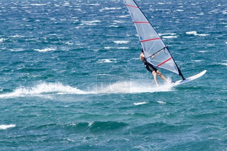 Photo for Lone windsurfer in the ocean catching a wave - Royalty Free Image