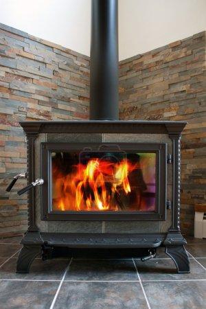 Photo pour Un nouvelle fonte poêle à bois brûlants avec la tuile d'ardoise. - image libre de droit
