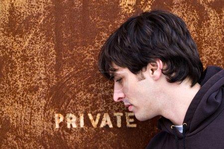 Photo pour Un jeune homme debout devant une vieille porte ou une entrée qui lit PRIVÉ. Une excellente image pour tout concept de vol d'identité . - image libre de droit