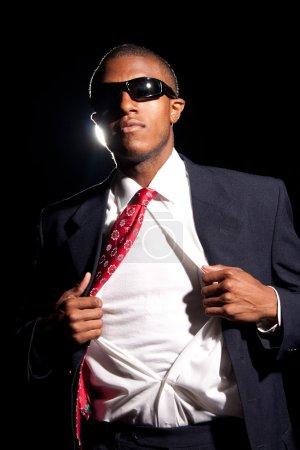 Photo pour Un jeune homme d'affaires afro-américain déchirer sa chemise ouverte pour révéler le t-shirt en dessous. Ajoutez votre texte ou votre illustration pour personnaliser facilement le message . - image libre de droit