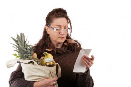 Photo pour Milieu femme âgée examinant soigneusement sa caisse en examinant sa facture d'épicerie. - image libre de droit
