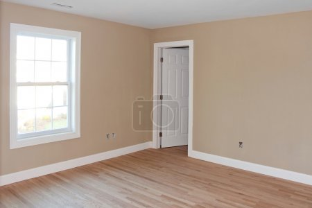 Photo for Newly constructed house interior room with unfinished wood floors window and closet door. Electrical connections are partially unfinished. - Royalty Free Image