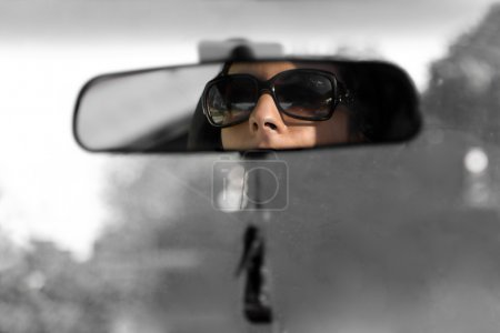 Photo for The face of a young woman driving as seen in the rear view mirror in isolated color. - Royalty Free Image