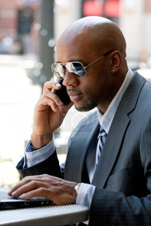 Photo for A business man in his early 30s talking on his cell phone and working on his laptop or netbook computer. - Royalty Free Image