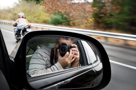 Photo for A paparazzi photographer takes a photo of a woman driving a motorcycle on the highway. Shallow depth of field. - Royalty Free Image