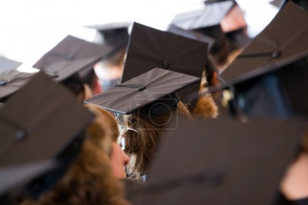 Photo for A group of college or high school graduates wearing the traditional cap and gown. Shallow depth of field. - Royalty Free Image