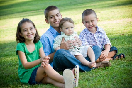 Photo pour Un groupe de quatre enfants avec une fille et trois garçons. Frères et sœurs s'entendent bien. Profondeur de champ peu profonde avec un accent aigu sur les garçons . - image libre de droit