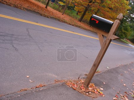 A mailbox near the road with some nice fall foliag...