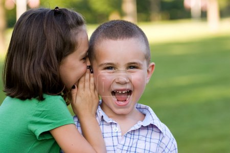 Photo for A young girl telling her brother a secret. - Royalty Free Image